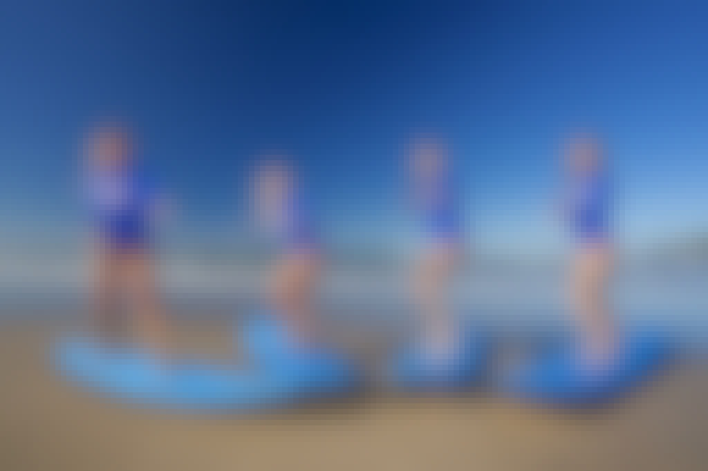 4 girls standing on surfboards on the beach